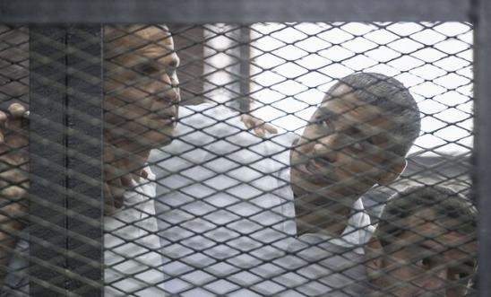 Peter Greste, Mohamed Fahmy y Baher Mohamed escuchan el veredicto en la sala del juicio. Foto: AFP/Getty Images